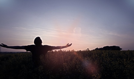 A silhouetted man holding his arms out whilst in a grassy meadow Stock Photo