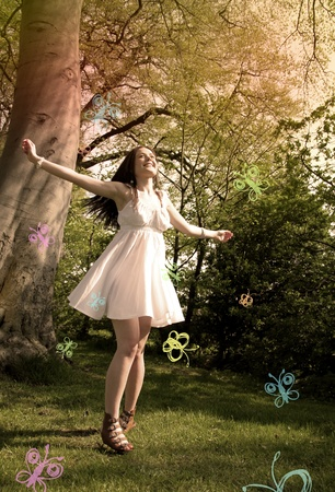 expressing positivity: a young woman dances around in a forest, with illustrated butterfies flying around her. Stock Photo