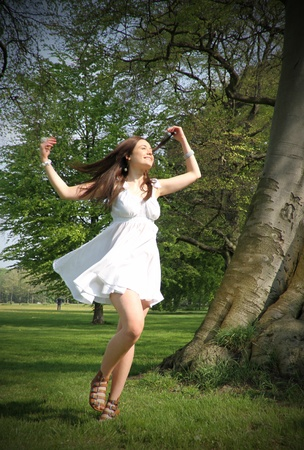 a young woman dances infront of a tree showing that she enjoying the summer sun. Please view my portfolio for similair images Stock Photo