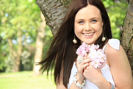 summer's: a happy woman holds and small bunch of flower close to her as she is enjoying a summers day.