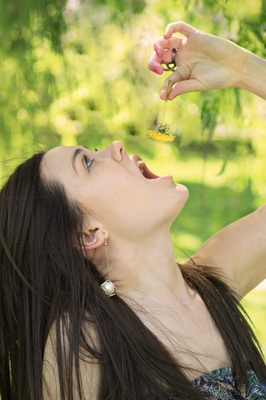 lean back: A woman lean back and attemps to eat a yellow flower.
