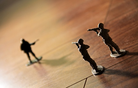 two toy soldiers ready to capture an opposing toy soldier on his own.