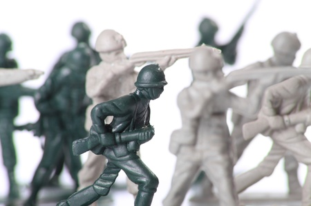 a small group of toy soldiers run to battle against a white background.