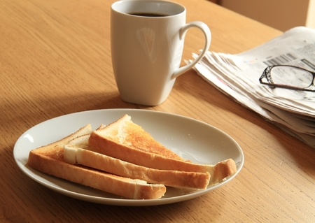 a breakfast set out on a table lit from the morning sun beaming through the blinds. The shot contains coffee,toast on a plate,glasses and a newspaper