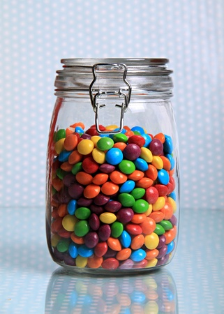 A massive jar of small multicoloured sweets on a shiny surface with a dotted background