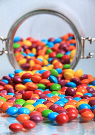 multi coloured rainbow sweets spilling out of the big sweet jar on to a shiny surface.