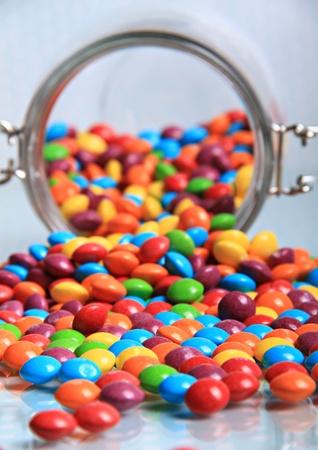 multi couleur bonbons arc-en-ciel déversant de gros pot sucré à une surface brillante.