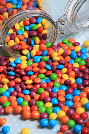 multi coloured rainbow sweets spilling out of the big sweet jar on to a shiny surface. Stock Photo