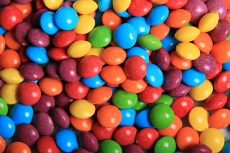 A bright and colourful close up image of hundreds of tiny rainbow sweets.
