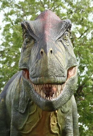 a scary model dinosaur looking straight at the camera with big sharp teeth photo
