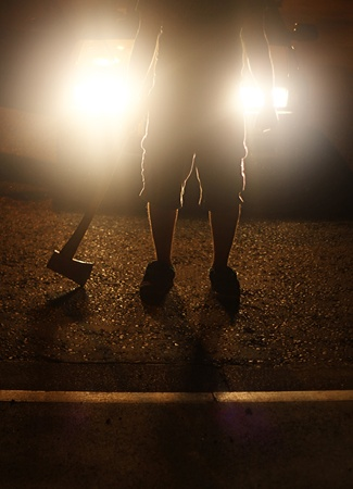 headlights: a maniac standing infront of a car with a axe whilst the headlights are beaming bright. Stock Photo