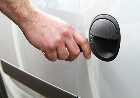 a man locks his car door with his key shot in daylight. Stock Photo