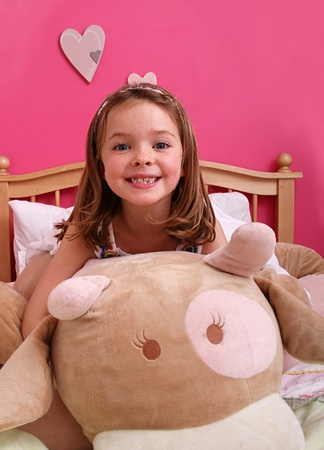 a really cute young girl playing with a giant teddy in a girly pink room whilst sat on a bed.