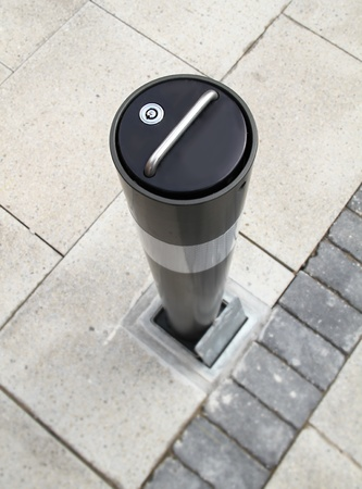 certain: image of a brand new security bollard on a street used to stop access of vehicles in certain areas