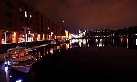 an image of the albert docks in liverpool all lit up at night with lovely light reflections in the water.no property release required.