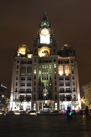 a full front shot of the iconic liverpool liver building at the docks lit up at night