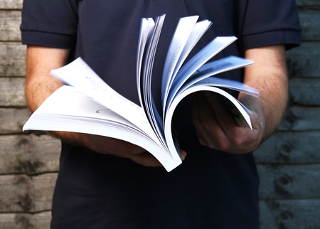a young man flips through a book in his hand with motion blur on the pages. photo