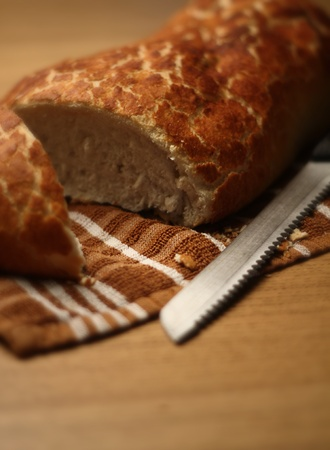 a loaf of bread cut open on a table with a knife next to it. images was shot at F1.8 for extreme soft focus look.