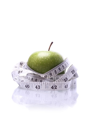 body concern: Close-up of an apple with a measuring tape around it several times with a reflection. Stock Photo