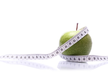 body concern: Close-up of an apple with a measuring tape wrapped around it with a reflection. Stock Photo