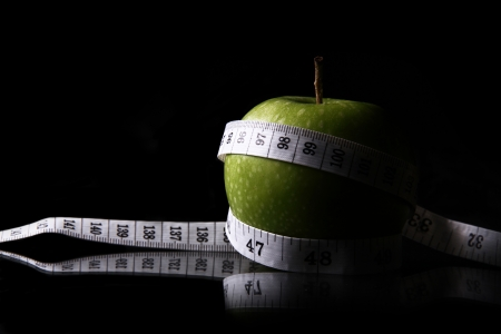 Close-up of an apple with a measuring tape wrapped around it with a reflection. Stock Photo
