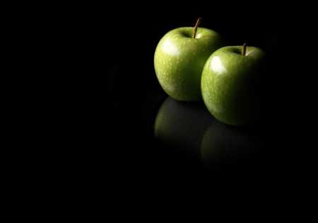 body concern: two apples lay on a reflective surface lit by one light with lots of copy space.