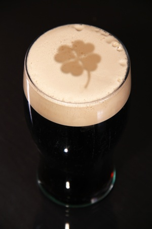 A pint of irish stout for St. patrick day, with a clover imprinted in the head of the beer. photo