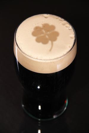 Une pinte de stout irlandaise de Saint Patrick jour, avec un trèfle gravé dans la tête de la bière.