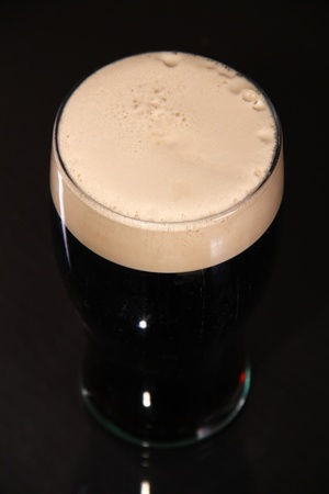 cerveza negra: Una pinta de cerveza negra irlandesa de San Patricio día sobre un fondo oscuro