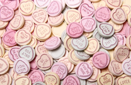 a full image caption containing hundreds of multi coloured sweets with hearts on.