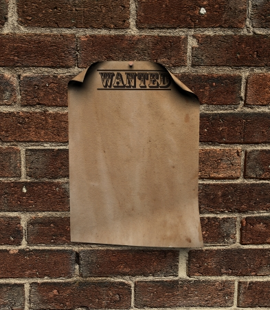 a computer generated wanted poster pinned up on a brick wall  photo