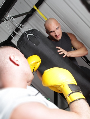 punching bag: Two men train for boxing using a punch bag and gloves Stock Photo