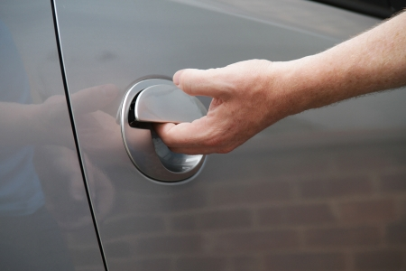 a shot of a man getting into a car by lifting the door handle