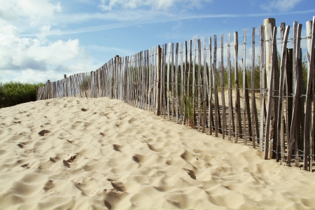 fence running along a sandy beach on a sunny day with a bright blue sky, formby beach in england Stock Photo - 15642956