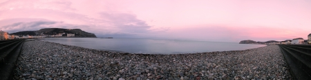 a panoramic shot of llandudno pebble beach at sunset
