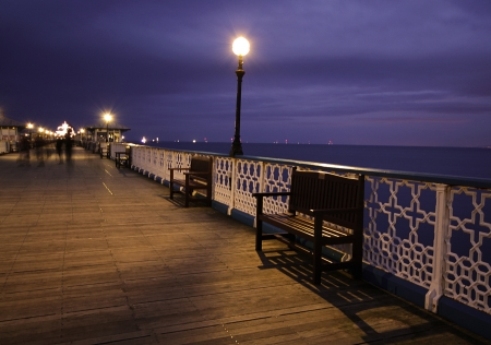 image shows a bench on a English promanade at night