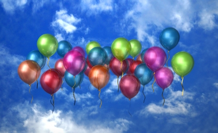 A large group of balloons floating in the bright blue sky with clouds