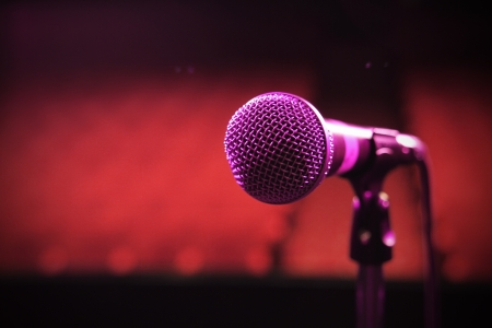 a shot of a microphone on its own on a stage lit up by a red and blue light