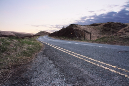 Image of an English road disappearing in to the horizon through the hills at sunset  Stock Photo