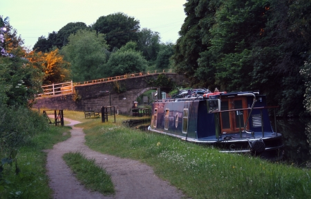 And barge is tied up to the bank of the canal at night shot on a slow shutter speed   Stock Photo