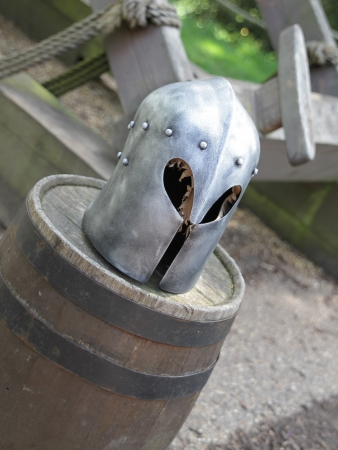Knights helmets placed on a barrel in the daytime