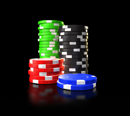 Different colour poker chips stacked up symbolising gambling against a black background. Stock Photo