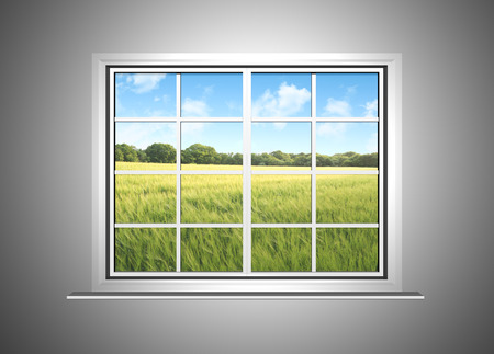 A beautiful view from a closed window inside a house showing a scenic farmers field with blue skies. Stock Photo
