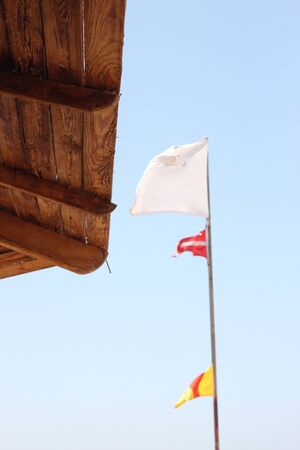 White flag and part of the tent on the beach