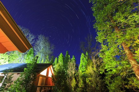star trail: Wooden house with star trail at Bass Lake, California Editorial