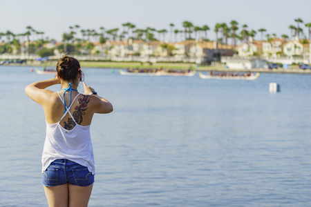 dragonboat: A woman taking picture of dragonboat competition at Long Beach, Los Angeles