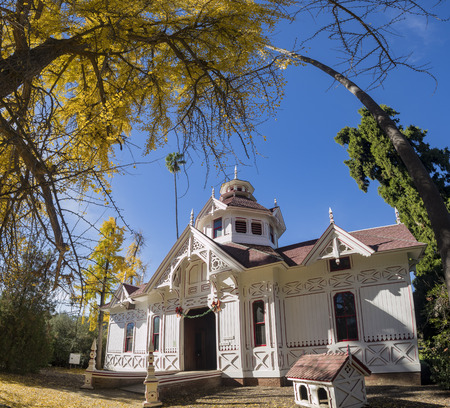 Beautiful fall color in park with Queen Anne Cottage, blue sky, Arcadia, California