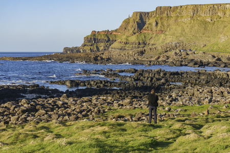 Photographer taking picture of the famous ancient volcanic eruption - Giants Causeway of County Antrim, Northern Ireland Stock Photo