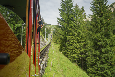 People taking the scenic view from the special train climbing up to the Mount Pilatus, Lucerne, Switzerland Stock Photo