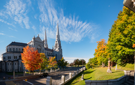 Exterior morning view of the Basilica of Sainte-Anne-de-Beaupre church with red maple tree at Quebec, Canada Фото со стока